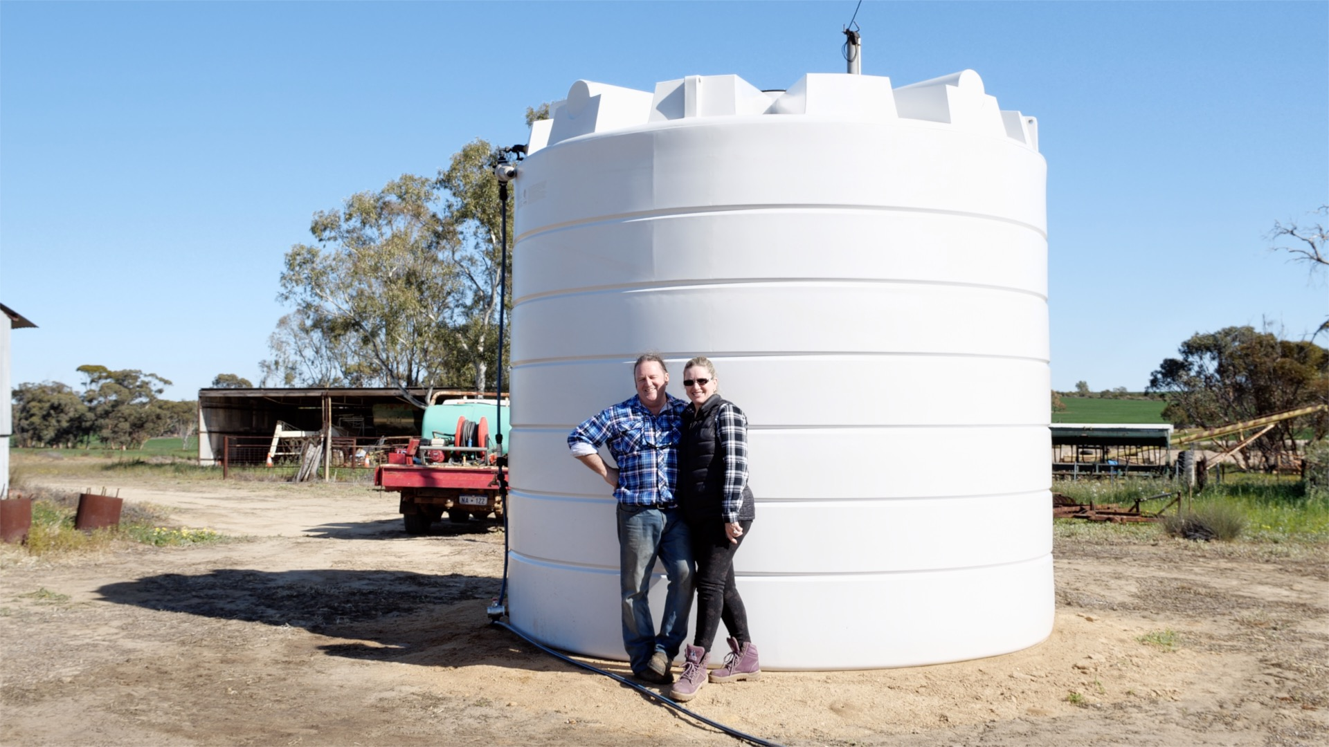 Man and woman smiling in front of their poly water tank